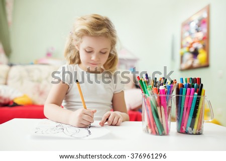 Portrait of child blonde girl drawing at home in her room - stock photo
