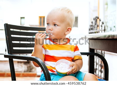 Portrait of child eating ice cream. Outdoor at the cafe - stock photo