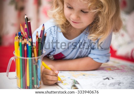 Portrait of child girl drawing with colorful pencils - stock photo