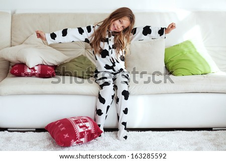 Portrait of child in soft warm cow print pajamas waking up at morning - stock photo
