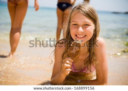 Portrait of child lying on the beach and eating ice cream
