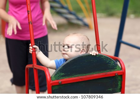 Portrait of child on a swing at playground - stock photo