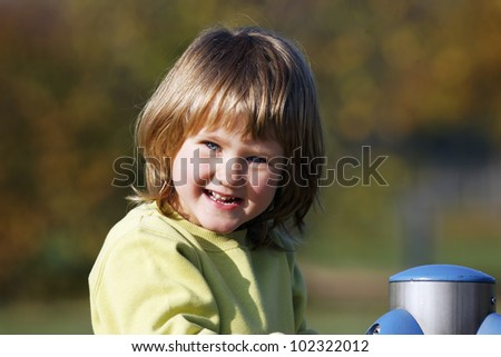 portrait of child playing on colorful playground - stock photo