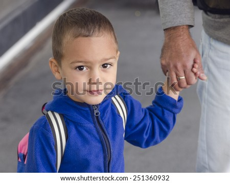 Portrait of  child toddler, boy or girl, holding a hand of father. - stock photo