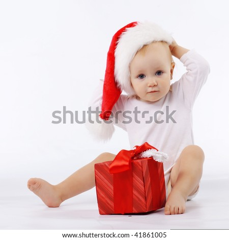 Portrait of child wearing santa hat sitting near red gift box in white studio - stock photo