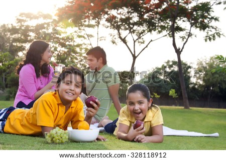 Portrait of children eating fruit - stock photo