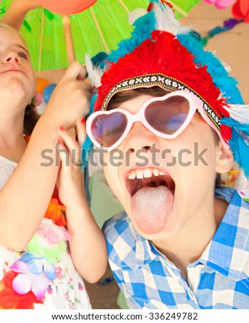 Portrait of children friends at a birthday party with boy pulling faces and sticking tongue out, dressing up in colorful fancy dresses, joyfully fun together. Kids expressions lifestyle home garden. - stock photo