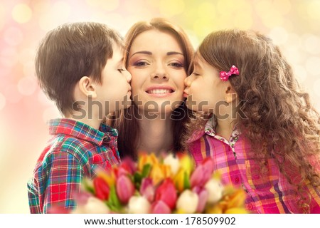 Portrait of children kissing her mother with flowers. Mother`s day concept. Family holiday - stock photo
