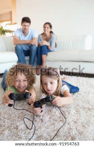 Portrait of children playing video games while their parents are watching in their living room - stock photo