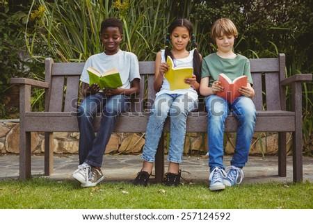 Portrait of children reading books at the park - stock photo
