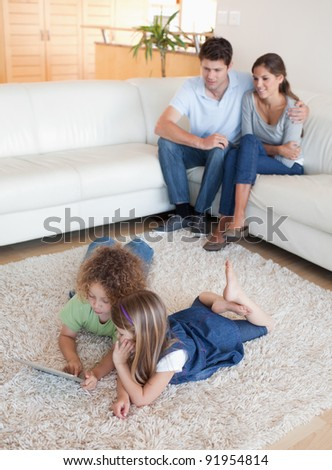 Portrait of children using a tablet computer while their happy parents are watching in their living room - stock photo