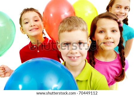 Portrait of children with balloons looking at camera