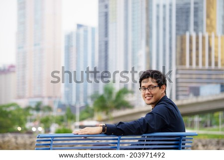 Portrait of chinese businessman sitting and relaxing on bench in Panama city with skyline and office buildings in background - stock photo