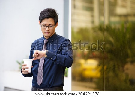 Portrait of chinese businessman standing near office building in Panama with coffee cup and checking the time on watch - stock photo