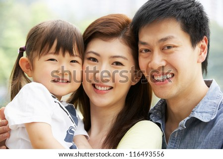 Portrait Of Chinese Family With Daughter In Park - stock photo