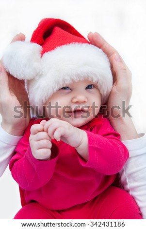 Portrait of Christmas baby is lying on motherâs hands - stock photo
