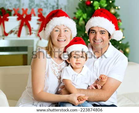 Portrait of Christmas happy family of three at home. Mother, father and son smiling, with Santa Hats, Christmas Tree and Chimney at background. - stock photo