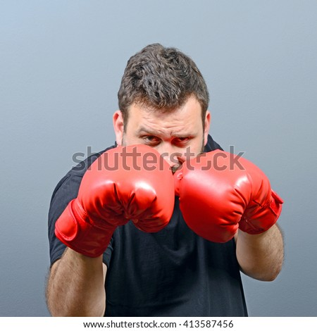 Portrait of chubby boxer posing with boxing gloves - stock photo