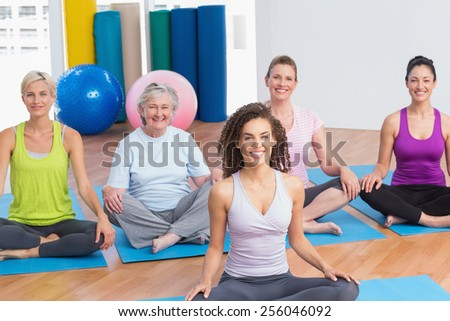 Portrait of class practicing yoga with instructor at gym - stock photo