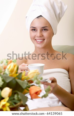 Portrait of clean girl with towel on head drinking tea in beauty salon - stock photo