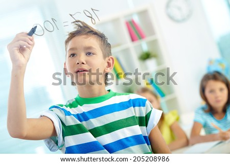 Portrait of clever boy doing sums on transparent board with schoolmates on background - stock photo