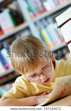 Portrait of clever boy looking at map in library - stock photo