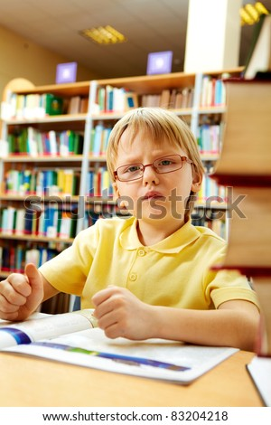 Portrait of clever boy reading in library