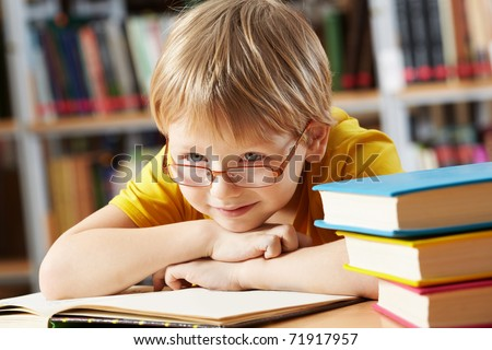 Portrait of clever boy with open book in library - stock photo