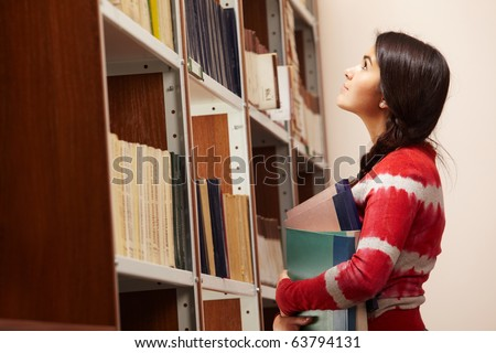 Portrait of clever girl choosing books in library - stock photo