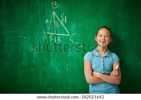 Portrait of clever schoolgirl with piece of chalk standing by the blackboard - stock photo