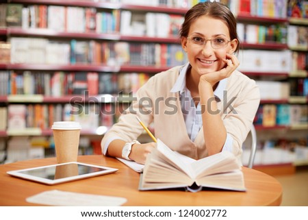 Portrait of clever student looking at camera and smiling in college library - stock photo