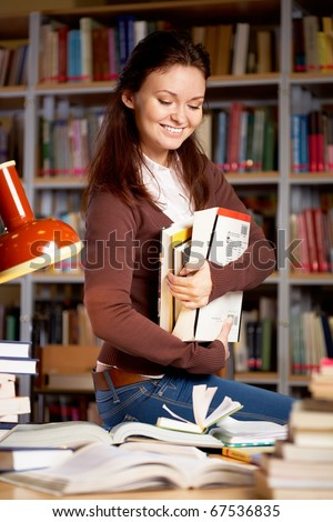 Portrait of clever student or young teacher with books smiling in college library - stock photo