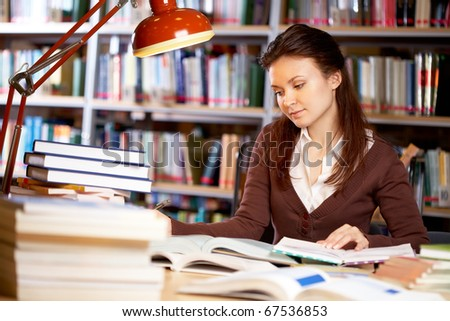 Portrait of clever student searching information for your report in college library - stock photo