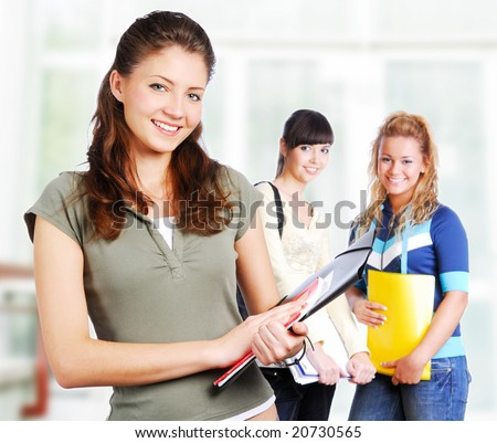 Portrait of clever students holding folder in hands - focus on foreground. - stock photo