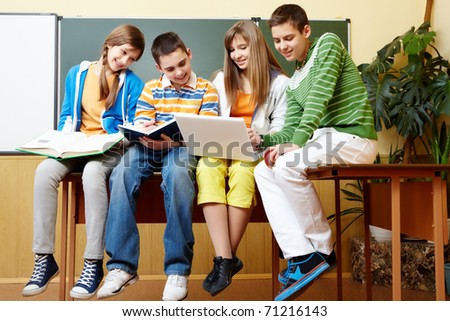 Portrait of clever students sitting in classroom and doing schoolwork - stock photo