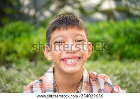 Portrait of close up 12 years old half - French, half - Thai boy smiling in the garden - stock photo
