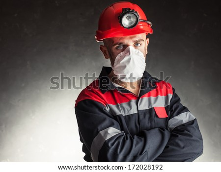 Portrait of coal miner with white respirator on his face against a dark background - stock photo