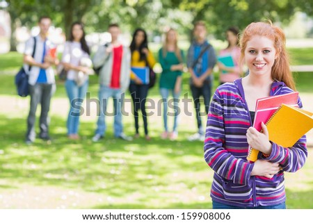 Portrait of college girl holding books with blurred students standing in the park - stock photo