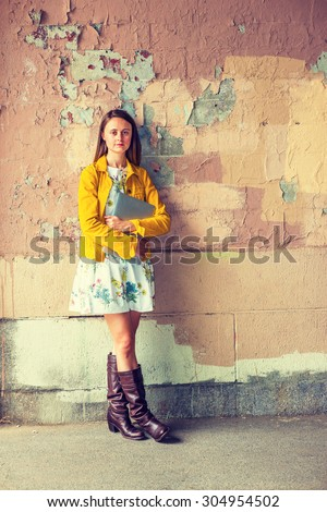 Portrait of College Student. A pretty girl wearing flower patterned underdress, yellow corduroy jacket, brown leather high riding boots, holding laptop computer, standing by wall peeling off paints. - stock photo