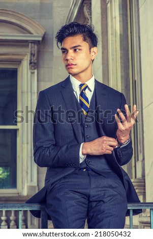 Portrait of College Student. Dressing in a black suit, patterned necktie, vest, a hand touching a cuff of sleeve, a young handsome businessman is standing by a railing in office building, thinking.  - stock photo