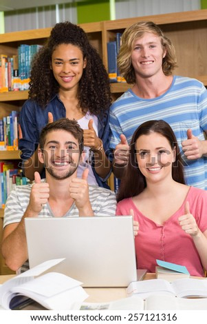 Portrait of college students gesturing thumbs up in the library - stock photo