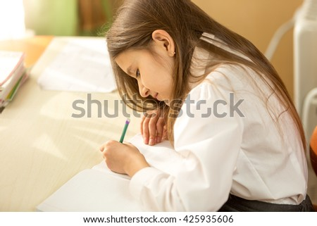 Portrait of concentrated schoolgirl doing homework at home - stock photo