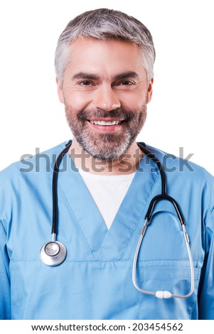 Portrait of confidence and experience. Portrait of happy mature surgeon in blue uniform looking at camera and smiling while standing isolated on white