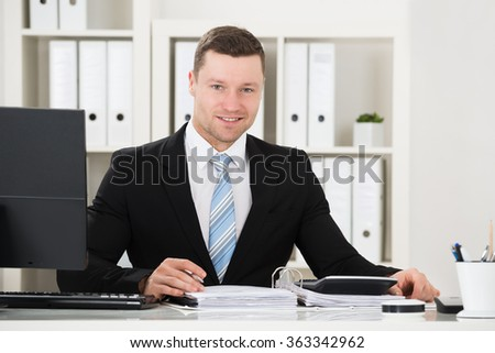 Portrait of confident accountant with calculator and documents at desk in office - stock photo