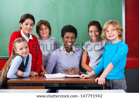 Portrait of confident African American female teacher and schoolchildren smiling together at desk in classroom - stock photo