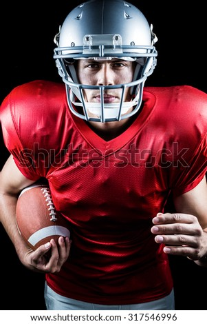 Portrait of confident American football player running while holding ball against black background - stock photo