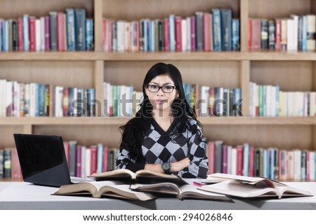 Portrait of confident asian female college student looking at someone in the library - stock photo
