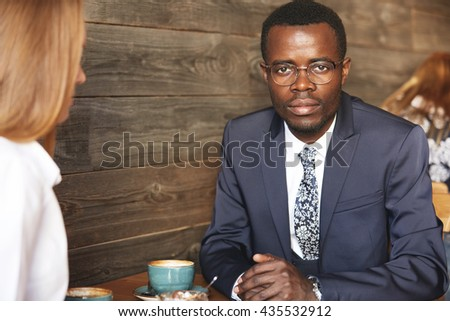 Portrait of confident attractive African businessman in glasses and formal suit looking at the camera, sitting at the table at a coffee while having business lunch with his redhead Caucasian partner - stock photo