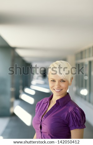 portrait of confident attractive business woman smiling and looking at camera out of office building. Copy space - stock photo
