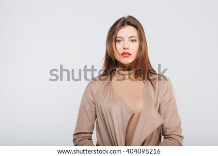 Portrait of confident attractive young businesswoman standing over white background - stock photo